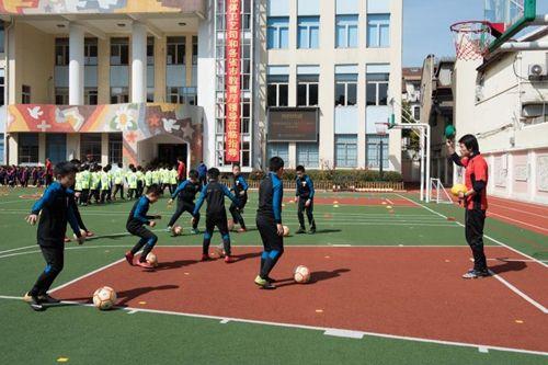 操场上,身着各色队伍的足球小将在老师的指导下训练。