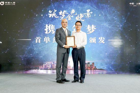 图为中国人寿上海市分公司总经理胡宏伟(左)向就职于交银施罗德基金公司的邱华先生颁发中国人寿税延养老年金保险首单纪念保单。