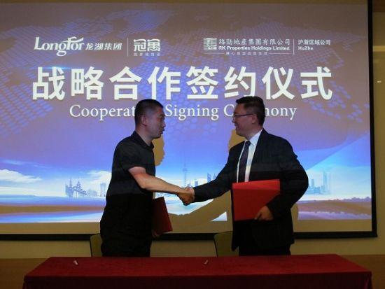 温介邦(左)与高大鹏现场签约后握手相庆。