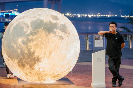图为:国际艺术家黄玉龙先生与装置艺术作品《Yue Liang》合影