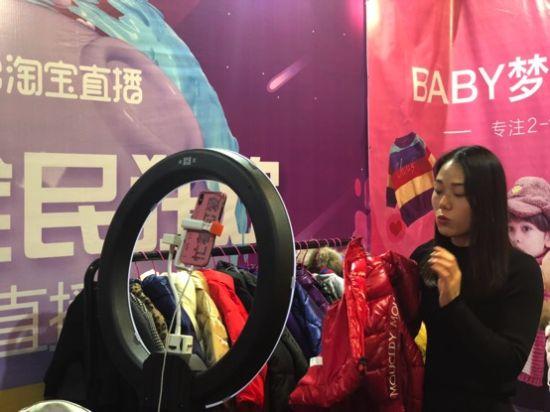 淘宝店主正在直播中展示衣服的品质。