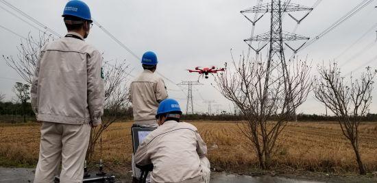 国网上海检修公司换流站运维人员与智能巡检机器人一起开展设备巡视。