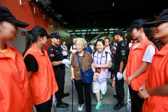 """2018年8月11日,""""张杰2018未・LIVE巡回演唱会""""登陆国家体育场,张杰高龄铁粉儿87岁的彭奶奶到现场观演。图为大麦网工作人员从检票口一路护送彭奶奶到座位。"""