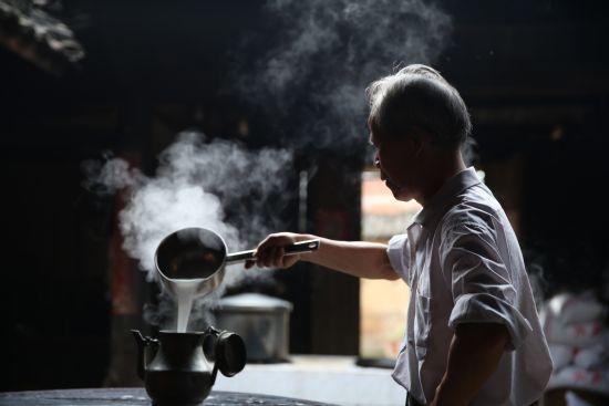 图/非遗技艺传承人、酒狐米酒的杨师傅在酿酒。