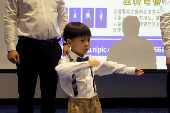 图:家长和孩子一起学习交通指挥手势。