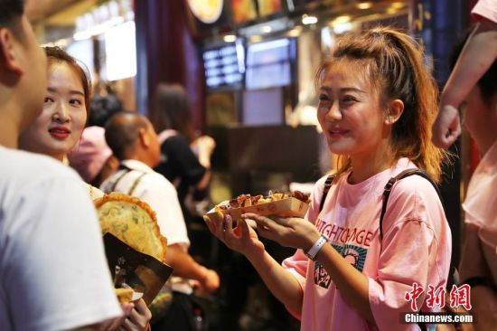 """游客在夜上海体验舌尖上的美妙""""食""""光。张亨伟 摄"""