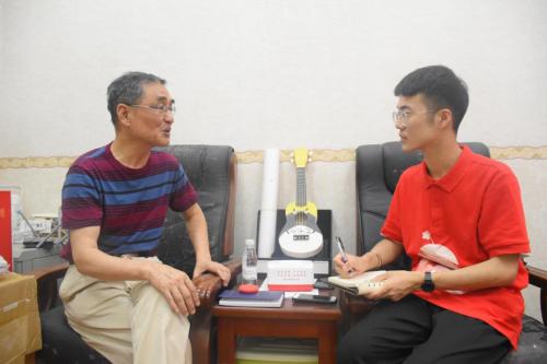 图为团队成员在采访社区达人杨启时。 黄秦勤 摄