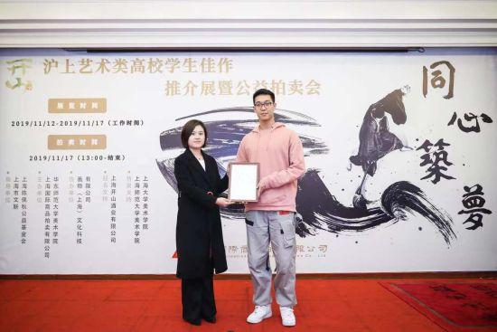 华东师范大学美术学院党委副书记刘麒(左)为获得一等奖的赵晋冀颁奖