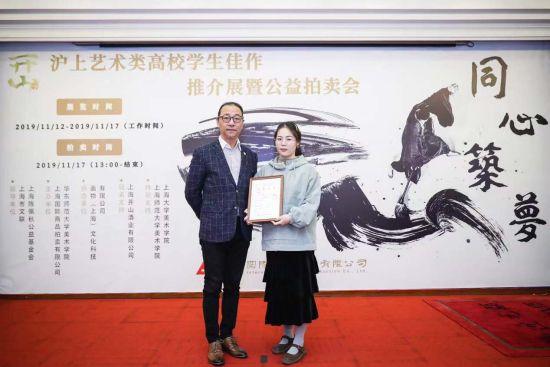 上海市文联副主席李守白(左)为特等奖获奖学生代表颁奖