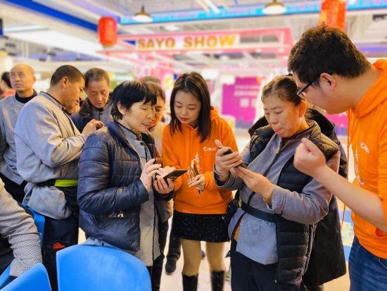 图:北京西铁营万达广场携程门店的员工正教授商场保洁人员通过智能返乡公益通道购买返乡火车(飞机)票。