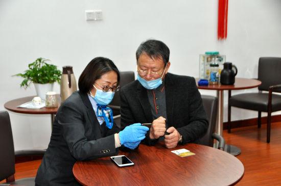 图:在农行工作人员指导下,奚老先生开通网银,向武汉中山博爱基金会账户捐赠人民币3万元。