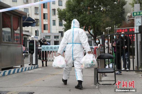 """11月23日,被列为中风险地区的上海顺和路126弄,该小区实行了""""只进不出""""的规定。图为工作人员为隔离居民递送物资。张亨伟 摄"""