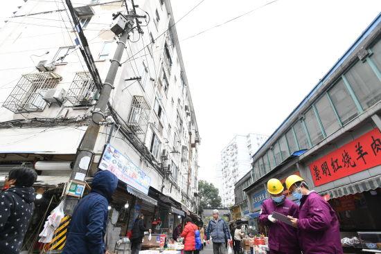 图:临近春节,国网上海浦东供电公司工作人员在潍坊小区附近的菜市场开展用电安全检查,让不停业的商户在节日里放心用电、安心营业。