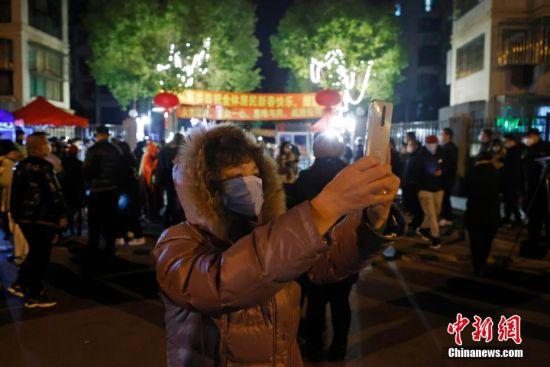 2月19日0时,市民从新高苑一期小区走出,用手机记录这一时刻。 殷立勤 摄