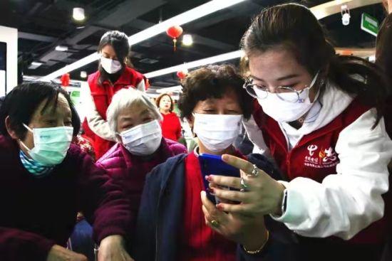 """图:全国劳动模范、上海电信一级客服专家邱莉娜为长宁区岐山村小区的长者们讲解""""健康码""""、""""行程码""""的调用方式,为他们送去疫情防控常态化下的关怀。"""