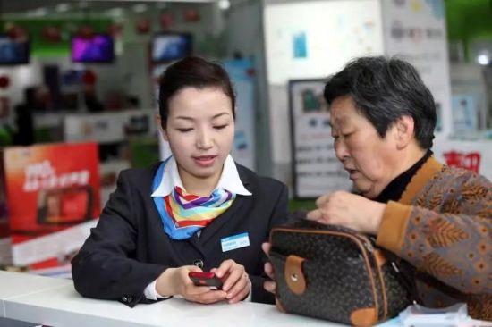 图:邱莉娜在手把手指导老年用户使用智能手机。