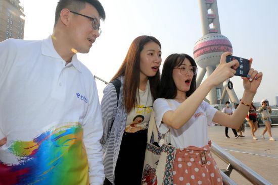 图:来上海游玩的年轻人,体验千兆Wi-Fi的极速下载乐趣。