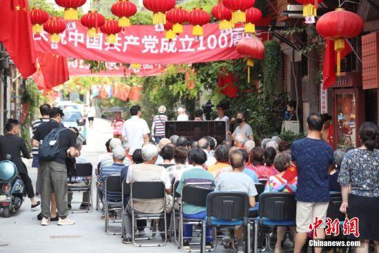 在上海虹口区恒丰里的弄堂里,邻里街坊们围着电视收看大会直播。 张亨伟 摄