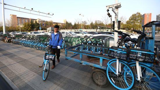 """图:在浙江杭州,哈��骑行运维人员正在后台""""哈��大脑""""指令下完成路面车辆调度工作。"""