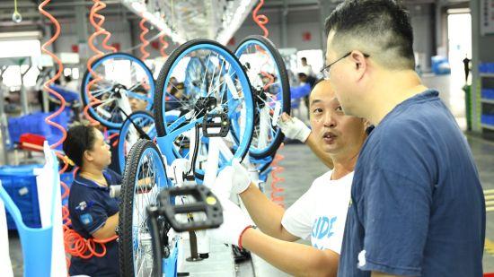 图:在广东佛山,哈��OEM整车供应商佛山金川科力远的生产线上,工作人员正在展示共享单车的生产流程。