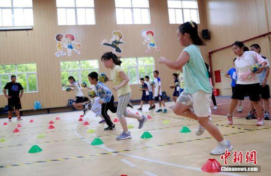 课后,学生在学校体育老师的带领下进行手球训练。 汤彦俊 摄