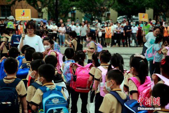 第一批结束课后服务的低年级小朋友放学回家。 汤彦俊 摄