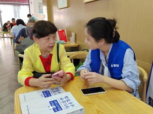 (蓝马甲志愿者为老人服务 记者 姜煜 摄)
